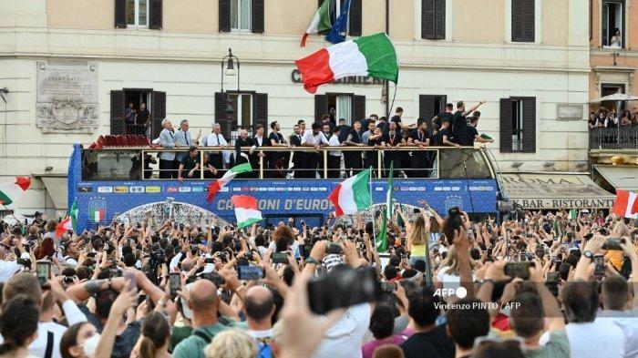 Para pemain tim nasional sepak bola Italia berparade dengan trofi UEFA EURO 2020 di atas bus tingkat Piazza Venezia di Roma pada 12 Juli 2021, sehari setelah Italia memenangkan pertandingan sepak bola final UEFA EURO 2020 antara Italia dan Inggris.