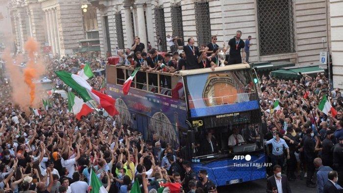 Para pemain tim nasional sepak bola Italia berparade dengan trofi UEFA EURO 2020 di atas bus tingkat di Roma pada 12 Juli 2021, sehari setelah Italia memenangkan pertandingan sepak bola final UEFA EURO 2020 antara Italia dan Inggris.