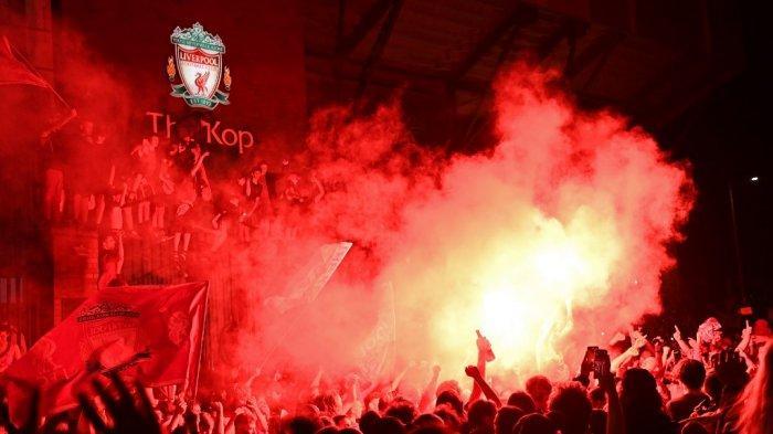 Fans merayakan Liverpool memenangkan gelar Liga Premier di luar stadion Anfield di Liverpool, barat laut Inggris pada 25 Juni 2020, menyusul kemenangan 2-1 Chelsea atas Manchester City. Liverpool dimahkotai juara Liga Premier tanpa menendang bola pada hari Kamis ketika kemenangan 2-1 Chelsea atas Manchester City mengakhiri 30 tahun menunggu The Reds untuk memenangkan gelar Inggris. Pasukan Jurgen Klopp memastikan gelar liga ke-19 untuk klub dengan rekor tujuh pertandingan tersisa setelah kekalahan City membuat mereka terpaut 23 poin dari Liverpool di puncak klasemen. Paul ELLIS / AFP