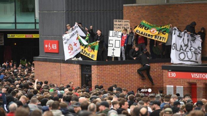Para pendukung memprotes pemilik Manchester United, di luar stadion klub Liga Utama Inggris Manchester United Old Trafford di Manchester, barat laut Inggris pada 2 Mei 2021, menjelang pertandingan Liga Utama Inggris melawan Liverpool. Manchester United adalah salah satu dari enam tim Liga Premier yang mendaftar ke turnamen Liga Super Eropa yang memisahkan diri. Tetapi hanya 48 jam kemudian Liga Super runtuh ketika United dan klub Inggris lainnya mundur.  Oli SCARFF / AFP