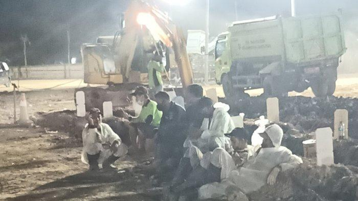 Para petugas penggali kubur tampak kelelahan menunggu mobil ambulans yang kembali