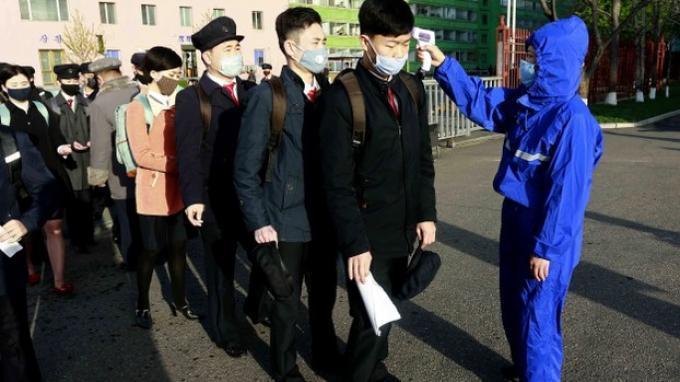 Para siswa yang mengenakan masker diperiksa suhu tubuhnya sebagai tindakan pencegahan terhadap virus corona ketika universitas mereka dibuka kembali setelah liburan, di Universitas Teknologi Kim Chaek di Pyongyang, Rabu, 22 April 2020.