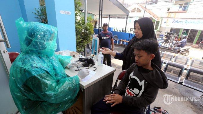 Paramedis Puskesmas Babakan Madang, Kabupaten Bogor, Jawa Barat, memeriksa pasien dengan menggunakan jas hujan sebagai alat pelindung diri (APD), Senin (30/3/2020). Dalam menghadapi wabah virus corona (Covid-19), petugas paramedis terpaksa menggunakan jas hujan sebagai usaha perlindungan diri karena APD medis terbatas cuma ada empat set yang dikirim oleh Dinkes Kabupaten Bogor. Warta Kota/Alex Suban
