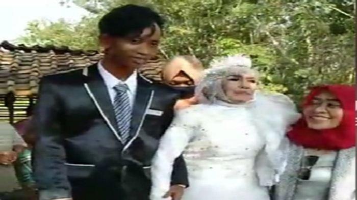 Pengantin beda usia Mbah Gambreng (65) dan Ardi (25) saat mengabadikan momen pernikahannya di Desa Bumi Harjo (Unit 7), kecamatan Lempuing, Kabupaten Ogan Komering (OKI).