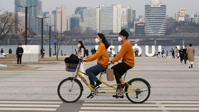Pasangan yang mengenakan masker naik sepeda tandem di sekitar taman di Seoul pada hari Sabtu. Lebih dari 7.000 orang di Korea Selatan telah didiagnosis dengan virus
