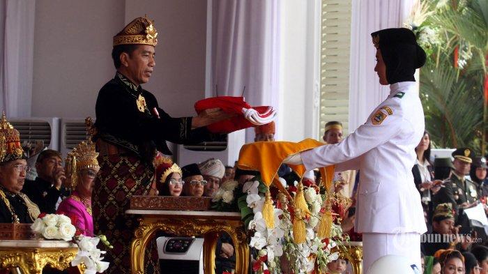Presiden Joko Widodo menyerahkan duplikat bendera pusaka kepada Paskibraka Salma El Mutafaqqiha Putri Achzaabi saat Upacara Peringatan Detik-detik Proklamasi Kemerdekaan Indonesia ke-74 Tahun 2019 di Istana Merdeka, Jakarta, Sabtu (17/8/2019). Upacara yang dipimpin oleh Presiden Jokowi tersebut dihadiri oleh perwakilan negara sahabat, tamu undangan, dan masyarakat umum. WARTA KOTA/HENRY LOPULALAN