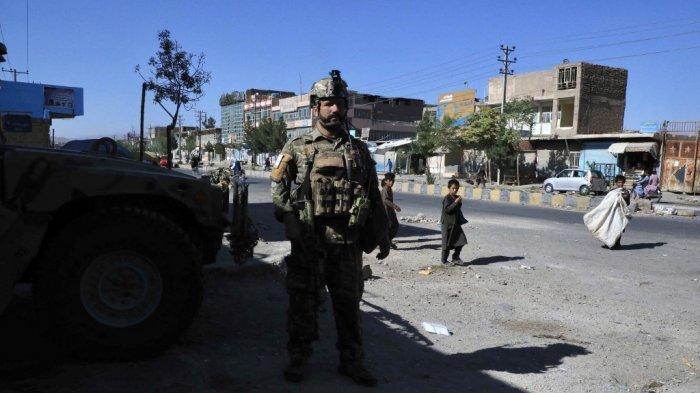 Seorang personel pasukan keamanan Afghanistan berjaga-jaga di sepanjang pinggir jalan di Herat pada 12 Agustus 2021, ketika Taliban mengambil alih markas polisi di Herat, kota terbesar ketiga di Afghanistan dan juga merebut ibu kota distrik utama lainnya yang hanya berjarak 150 kilometer dari ibu kota Kabul.