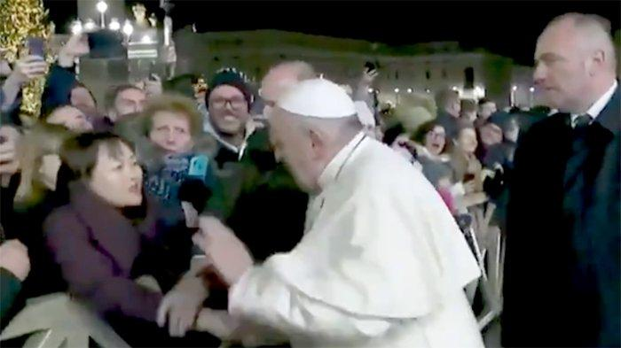 Paus Fransiskus memukul tangan warga China yang menarik tangannya tanggal  31 Desember malam ketika dia bertemu dengan masyarakat di Lapangan Santo Petrus.