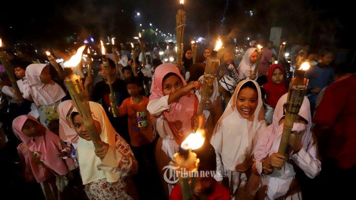 Sejumlah anak-anak saat melakukan pawai obor untuk menyambut malam takbiran di kawasan Matraman, Jakarta Timur, Selasa (4/6/2019). Selain membawa obor, pawai dimeriahkan dengan iringan alat musik beduk, bas, dan drum. Sepanjang rute pawai, takbir pun dikumandangkan. Tribunnews/Jeprima