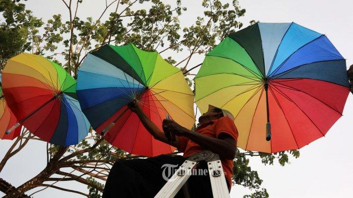 Hiasan payung dengan warna warni yang indah untuk dijadikan latar berfoto terbentang di kawasan Tugu Khatulistiwa, Jalan Khatulistiwa, Pontianak, Kalimantan Barat, Selasa (20/3/2018) sore. Hiasan ratusan payung ini dalam rangka menyambut event tahunan pesona titik kulminasi matahari yang jatuh pada tangga 21-23 Maret ini. TRIBUN PONTIANAK/DESTRIADI YUNAS JUMASANI