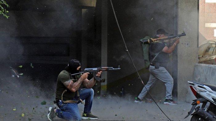 Pejuang Syiah dari gerakan Hizbullah dan Amal membidik dengan senapan serbu Kalashnikov dan peluncur granat berpeluncur roket di tengah bentrokan di daerah Tayouneh, di pinggiran selatan ibu kota Beirut, pada 14 Oktober 2021.