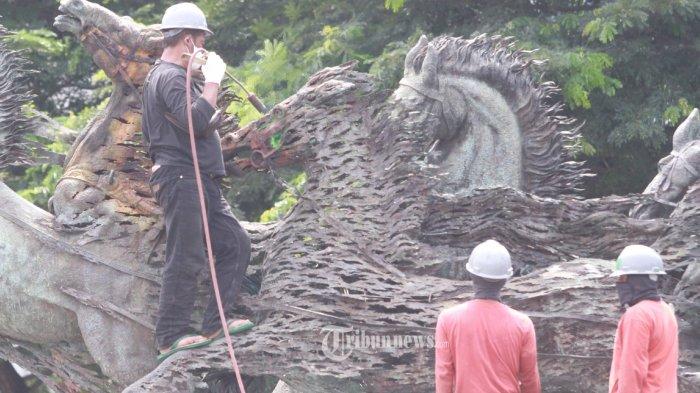 Sejumlah pekerja membersihkan patung kuda Arjuna Wijaya di Jalan Medan Merdeka, Jakarta, Rabu (27/1/2021). Patung yang dibangun sejak 1987 karya pematung Nyoman Nuarta tersebut dibersihkan dan ditata kembali untuk memperindah kota. WARTA KOTA/HENRY LOPULALAN