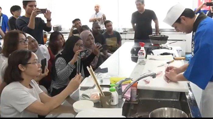 Para peserta dari Indonesia dan negara lain sedang memonitor dan memotret tukang ikan profesional saat memotong ikan tuna.