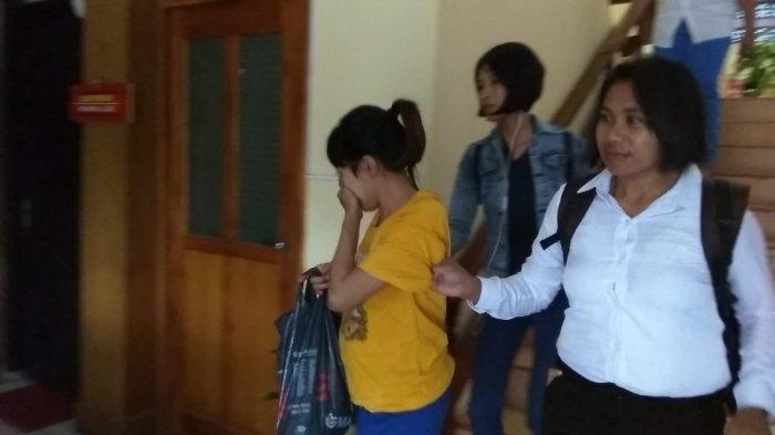 Pelaku pembunuhan bayi berusia 2 tahun (berbaju kuning), saat digelandang polisi menuju sel di Mapolres Kupang Kota, Kamis (2/2/2019).