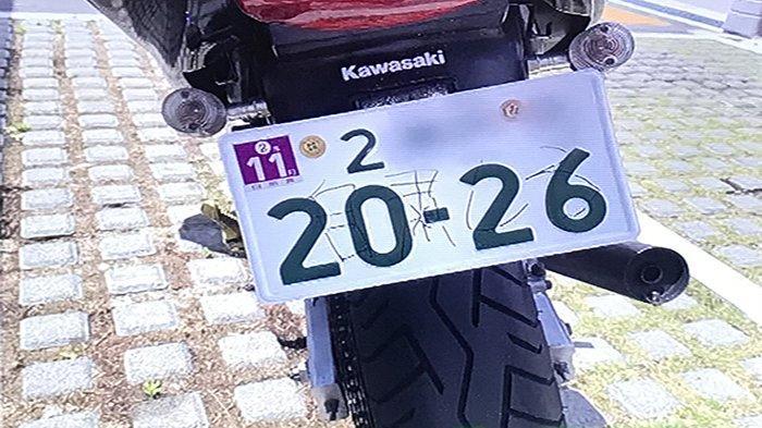 Coretan Jishuku (diam di rumah) pada pelat nomor sepeda motor Kawasaki di Tokyo.