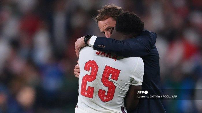 Pelatih Inggris Gareth Southgate berbicara kepada gelandang Inggris Bukayo Saka setelah kekalahan mereka dalam pertandingan final sepak bola UEFA EURO 2020 antara Italia dan Inggris di Stadion Wembley di London pada 11 Juli 2021.