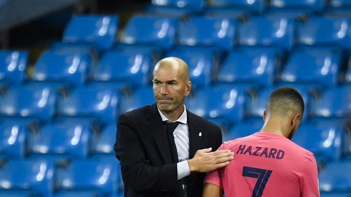 Pelatih Prancis Real Madrid Zinedine Zidane (Kiri) mengetuk penyerang Belgia Real Madrid Eden Hazard saat ia meninggalkan lapangan setelah digantikan selama pertandingan sepak bola leg kedua babak 16 besar Liga Champions antara Manchester City dan Real Madrid di Stadion Etihad di Manchester, Inggris barat laut pada 7 Agustus 2020. PETER POWELL / POOL / AFP