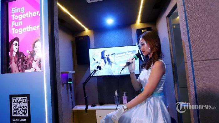 SPG saat mencoba kotak karaoke disela-sela peluncuran Mydio Sing Musictainment dikawasan Rawamangun, Jakarta Timur, Sabtu (10/4/2021). Mydio Sing Musictainment merupakan aplikasi karaoke keluarga yang memiliki ratusan ribu bank lagu, baik Indonesia maupun mancanegara. Di tengah PPKM yang diberlakukan pemerintah, aplikasi ini menjadi pilihan hiburan dengan sensasi karaoke keluarga yang dilengkapi dengan fitur dan perlengkapan menyanyi, dan dapat diakses dengan mudah melalui smartphone. Tribunnews/Jeprima