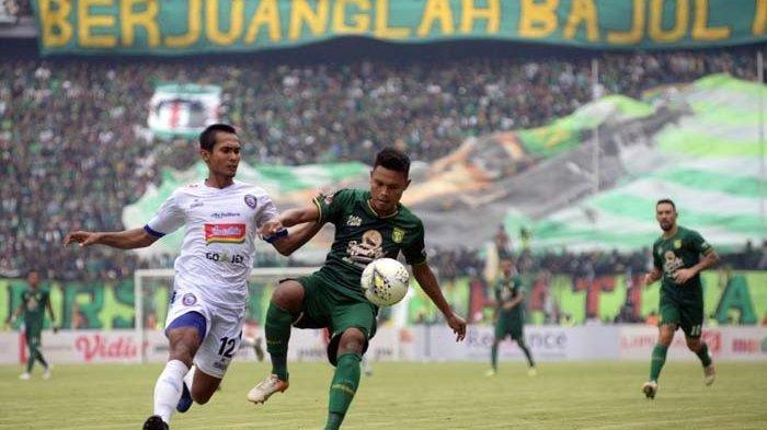 Pemain Arema FC, Hendro Siswanto (kiri) memenangi perebutan bola dengan pilar Persebaya Fandi Eko Utomo.