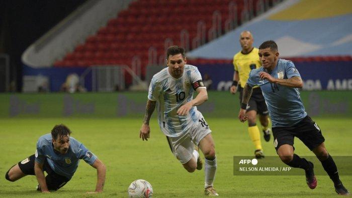 Pemain Argentina Lionel Messi (tengah) dan pemain Uruguay Lucas Torreira berebut bola saat pemain Uruguay Matias Vina (kiri) menyaksikan pertandingan fase grup turnamen sepak bola Conmebol Copa America 2021 di Stadion Mane Garrincha di Brasilia, pada 18 Juni 2021. NELSON ALMEIDA / AFP