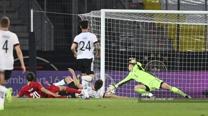 Pemain depan Denmark Yussuf Poulsen (kiri) mencetak gol penyeimbang 1-1 melewati kiper Jerman Manuel Neuer (kanan) selama pertandingan sepak bola persahabatan Jerman v Denmark di Innsbruck, Austria pada 2 Juni 2021, dalam persiapan untuk Kejuaraan Eropa UEFA. CHRISTOF STACHE / AFP