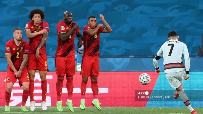Pemain depan Portugal Cristiano Ronaldo (kanan) melakukan tendangan bebas selama pertandingan sepak bola babak 16 besar UEFA EURO 2020 antara Belgia dan Portugal di Stadion La Cartuja di Seville pada 27 Juni 2021. LLUIS GENE / POOL / AFP