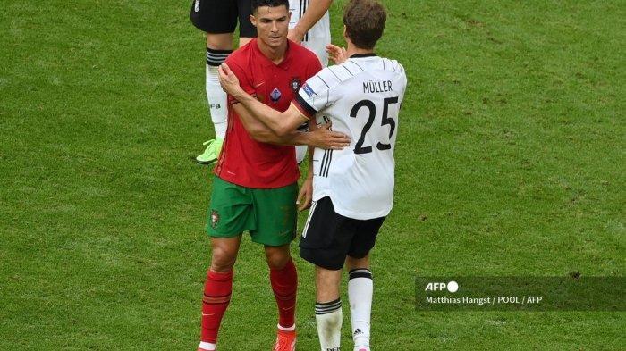 Pemain depan Portugal Cristiano Ronaldo (kiri) menyapa pemain depan Jerman Thomas Mueller (kanan) pada akhir pertandingan sepak bola Grup F UEFA EURO 2020 antara Portugal dan Jerman di Allianz Arena di Munich pada 19 Juni 2021.