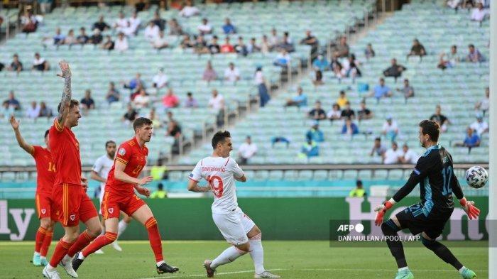 Pemain depan Swiss Mario Gavranovic (tengah) mencetak gol melewati kiper Wales Danny Ward, dari posisi offside, selama pertandingan sepak bola Grup A UEFA EURO 2020 antara Wales dan Swiss di Stadion Olimpiade di Baku pada 12 Juni 2021.