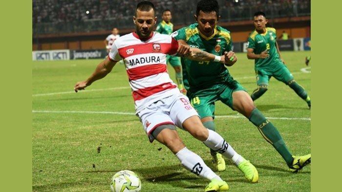 Pemain Madura United, Aleksandar Rakic (9) berusaha menguasai bola yang coba diganggu pemain Sriwijaya FC Muhammad Andes Adinata (94).