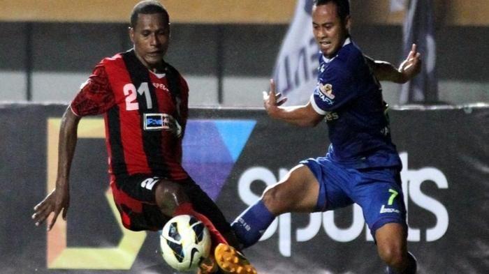 Pemain Persipura Yustinus Pae (merah-hitam) duel memperebutkan bola dengan gelandang Persib Atep