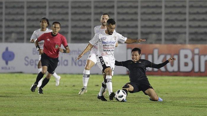 Pemain Timnas Indonesia U-23 Evan Dimas coba mengambil bola dari pemain Bali United, Diego Assis saat melakukan pertandingan uji coba di Stadion Madya, Minggu (7/3/2021) malam.