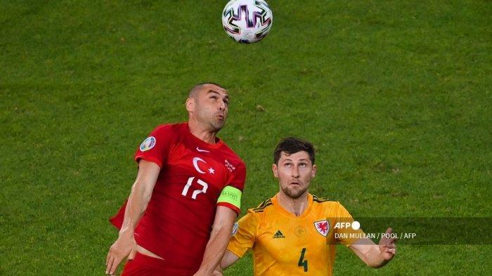 Penyerang Turki Burak Yilmaz (kiri) menyundul bola dengan bek Wales Ben Davies selama pertandingan sepak bola Grup A UEFA EURO 2020 antara Turki dan Wales di Stadion Olimpiade di Baku pada 16 Juni 2021.