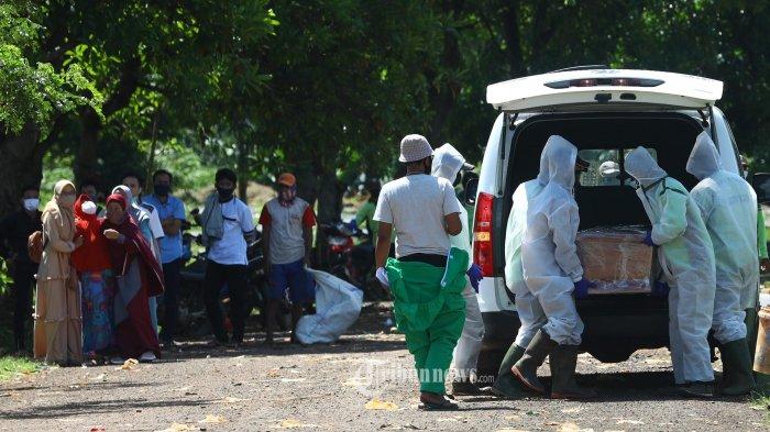 Petugas pemakaman membawa peti jenazah pasien COVID-19 di TPU Pondok Ranggon, Jakarta, Minggu (24/5/2020). Dalam data yang dihimpun hingga Minggu (24/5/2020) pukul 12.00, korban meninggal akibat pandemi Covid-19 di Indonesia mencapai 1372 orang. TRIBUNNEWS/IRWAN RISMAWAN