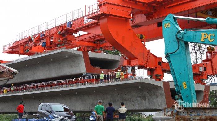 Pekerja melakukan proses pemasangan girder di lokasi proyek Kereta Cepat Indonesia China (KCIC) Bandung-Jakarta di Kelurahan Cirangrang, Kecamatan Babakan Ciparay, Kota Bandung, Jumat (3/1/2020). Pemasangan girder atau balok beton seberat lebih kurang 900 ton dengan panjang lebih dari 15 meter itu, membutuhkan waktu sekitar dua hari. (TRIBUN JABAR/GANI KURNIAWAN)