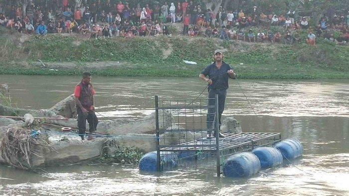 Proses pemasangan perangkap besi untuk menyelamatkan buaya berkalung ban di Sungai Palu, Selasa (11/2/2020) sore.