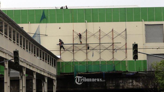 Sejumlah pekerja menyelesaikan proyek pembangunan jembatan penghubung antara Blok F dan Blok G Pasar Tanah Abang, Jakarta Pusat, Selasa (22/1/2019). Pembangunan yang sempat mangkrak sejak tahun 2013 tersebut, kini mulai diselesaikan. Warta Kota/Angga Bhagya Nugraha
