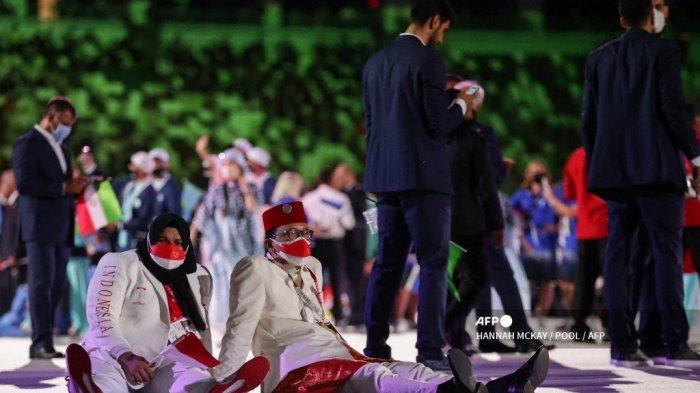 Anggota delegasi Indonesia duduk di lantai selama upacara pembukaan Olimpiade Tokyo 2020 parade atlet, di Stadion Olimpiade Tokyo pada 23 Juli 2021.