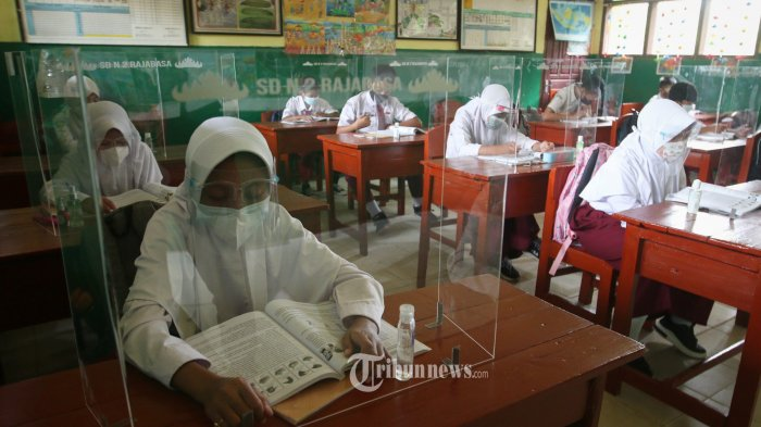 PTM PELAJAR - Siswa mengikuti pembelajaran tatap muka (PTM) di UPT SD Negeri 2 Rajabasa, Senin (13/9/2021).  Seiring penurunan status pandemi dari zona merah ke zona kuning atau dari Pemberlakuan Pembatasan Kegiatan Masyarakat (PPKM) level 4 menjadi PPKM level 3 di Kota Bandar Lampung, pembelajaran tatap muka dilakukan secara terbatas yang diikuti hanya 50 persen siswa. Selain itu selama pembelajaran berlangsung selama 2x60 menit sehari dan berlaku di seluruh jenjang pendidikan setempat, mulai tingkat SD, SMP dan SMA .(Tribunlampung.co.id/Deni Saputra)