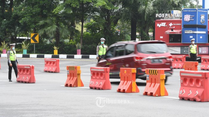 PETUGAS BERJAGA - Petugas gabungan saat stand by di pintu masuk Surabaya di bundaran Waru pada Pemberlakuan Pembatasan Kegiatan Masyarakat (PPKM) hari pertama, Senin (11/1). SURYA/AHMAD ZAIMUL HAQ