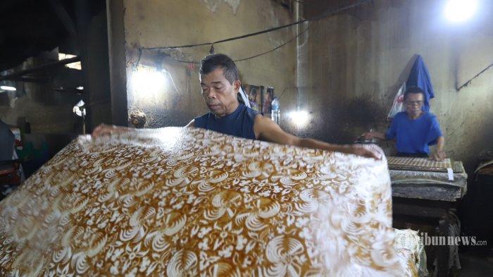 Pekerja menyelesaikan pembuatan sarung dengan motif batik di La Gurda, Jayengan, Serengan, Kota Solo, Jawa Tengah, Selasa (20/4/2021).