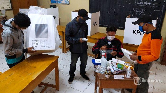 Petugas Kelompok Penyelenggara Pemungutan Suara (KPPS) mempersiapkan logistik Pemilihan Kepala Daerah (Pilkada) 2020, baik perlengkapan pemungutan suara maupun alat pelindung diri (APD) untuk penyelenggaraan Pemilihan Bupati dan Wakil Bupati (Pilbup) Kabupaten Bandung 2020 saat pembuatan Tempat Pemungutan Suara (TPS) 43 di RT 05 RW 02, Kampung Cilebak, Desa Rancamanyar, Kecamatan Baleendah, Kabupaten Bandung, Jawa Barat, Selasa (8/12/2020). Pilkada 2020 serentak diselenggarakan di seluruh Indonesia pada 9 Desember 2020, termasuk di Kabupaten Bandung yang diikuti tiga pasangan calon (paslon), yakni nomor urut 1 Nia Kurnia Agustina-Usman Sayogi, nomor urut 2 Yena Iskandar Ma'soem-Atep Rizal, dan nomor urut 3 Dadang Supriatna-Syahrul Gunawan. Pelaksanaan Pilkada 2020 yang berlangsung pada masa pandemi Covid-19 harus menerapkan protokol kesehatan untuk mencegah penyebaran Covid-19. Tribun Jabar/Gani Kurniawan