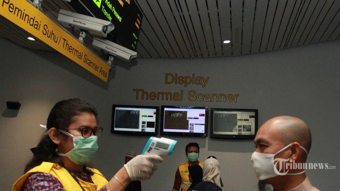Petugas dari Kantor Kesehatan Pelabuhan (KKP) Klas 1 Soetta melakukan pemeriksaan suhu tubuh crew pesawat maskapai asing setibanya di Terminal 3 Bandara Soekarno Hatta, Tangerang, Banten, Senin (3/3/2020). Kantor Kesehatan Pelabuhan (KKP) Soekarno Hatta kini melakukan tiga lapis pemeriksaan bagi seluruh penumpang yang tiba mulai dari pemeriksaan riwayat perjalanan, riwayat kesehatan hingga pemeriksaan suu tubuh yang kesemua itu merupakan prosedur yang harus dijalankan untuk pencegahan dini penyebaran virus corona. TRIBUNNEWS/IRWAN RISMAWAN
