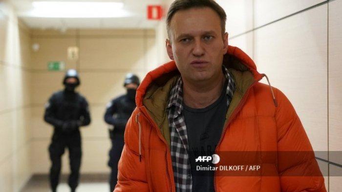 Pemimpin oposisi Rusia Alexei Navalny berdiri di dekat aparat penegak hukum di lorong sebuah pusat bisnis, yang merupakan kantor Yayasan Anti-Korupsi (FBK) miliknya, di Moskow pada 26 Desember 2019.