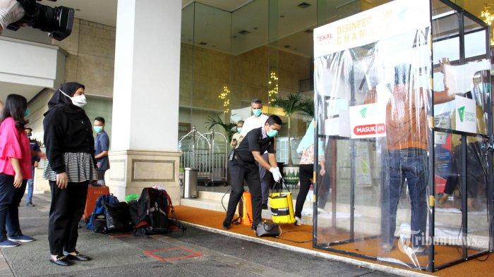 Sejumlah tenaga medis mengantre untuk disemprot cairan disinfektan saat akan memasuki Hotel Grand Cempaka, Jakarta Pusat, Kamis (26/3/2020). Pemprov DKI Jakarta menyiapkan hotel secara gratis untuk tenaga medis di Jakarta yang menangani pasien yang terinfeksi virus corona (Covid-19). Warta Kota/Angga Bhagya Nugraha