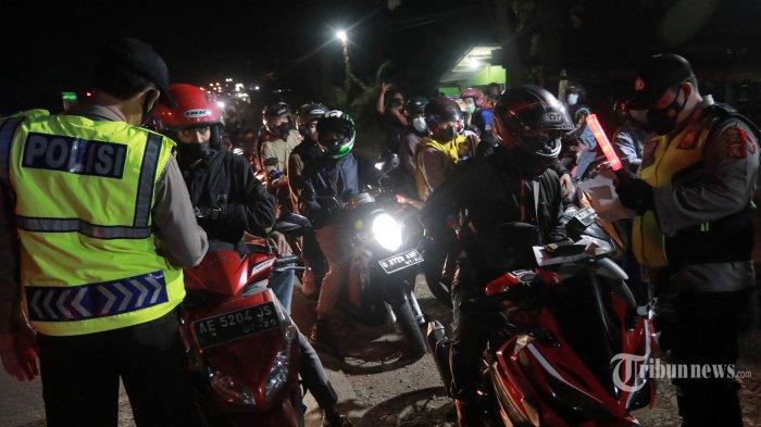 Petugas gabungan melakukan penyekatan pemudik di Pos Gamon, Karawang, Jawa Barat, Sabtu (8/5/2021) malam. Dalam penyekatan pemudik yang mayoritas pengendara roda dua tersebut, pemudik diarahkan untuk memutar balik menuju Jakarta, namun banyak pemudik yang menerobos penyekatan ini. Tribunnews/Irwan Rismawan