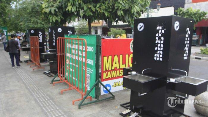 Warga mencoba menggunakan alat cuci tangan yang baru dipasang di kawasan Malioboro, Kota Yogyakarta, Kamis (10/12/2020). Sebanyak 34 alat yang tiap alat memiliki 4 titik kran air tersebut dipasang disepanjang Malioboro untuk memudahkan pengunjung mencuci tangan demi menjaga protokol kesehatan. (TRIBUN JOGJA/Hasan Sakri Gozali)