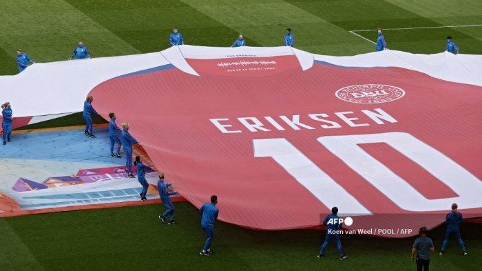 Penampil menampilkan spanduk yang menggambarkan jersey gelandang Denmark Christian Eriksen yang menderita serangan jantung saat pertandingan penyisihan grup menjelang pertandingan sepak bola babak 16 besar UEFA EURO 2020 antara Wales dan Denmark di Johan Cruyff Arena di Amsterdam pada 26 Juni 2021. Koen van Weel / POOL / AFP