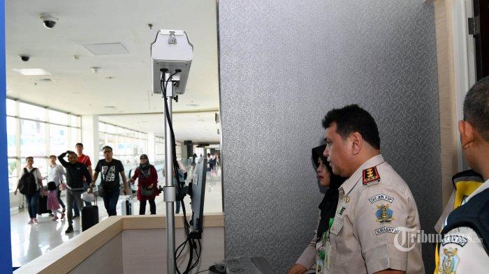 Petugas mengoperasikan alat pendeteksi suhu tubuh (thermal scanner) saat penumpang pesawat tiba di terminal 2 Bandara Juanda Surabaya, Rabu (22/1/2020). Kantor Kesehatan Pelabuhan (KKP) Kelas 1 Surabaya wilayah kerja bandara Juanda meningkatkan kewaspadaan dengan memasang alat pendeteksi suhu tubuh (thermal scanner) untuk mengantisipasi masuknya virus corona yang berasal dari negara China ke wilayah Indonesia. SURYA/AHMAD ZAIMUL HAQ (SURYA/AHMAD ZAIMUL HAQ)