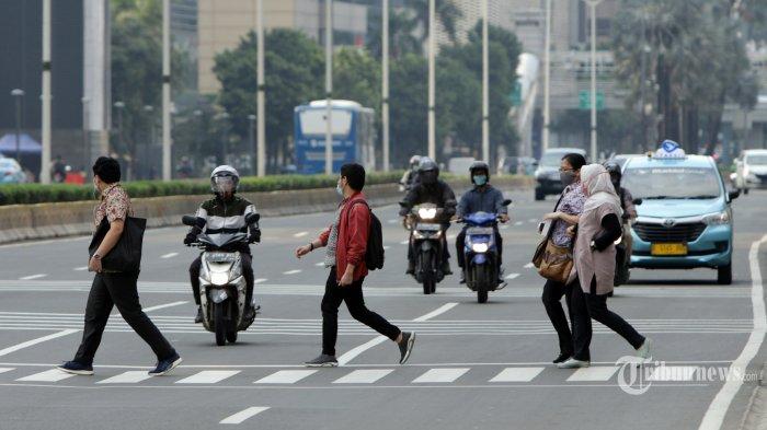 Suasana warga melintas di Jalan MH Thamrin Jakarta, Rabu (13/5/2020). Pemprov DKI Jakarta mulai menerapkan sanksi kepada warga yang melanggar penerapan pembatasan sosial berskala besar (PSBB) mulai dari aturan berkendara hingga pemakaian masker di luar rumah. Sanski tersebut berupa teguran hingga denda uang. TRIBUNNEWS/HERUDIN