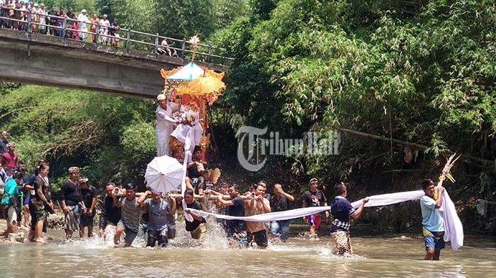 Sejumlah warga mengusung abu jenazah Dewa Yoga melewati sungai menuju Setra Banjar Adat Tegal Ambengan, Dusun Sakeh, Desa Sudimara, Tabanan, Rabu (10/10/2018). TRIBUN BALI/MADE PRASETYA ARYAWAN
